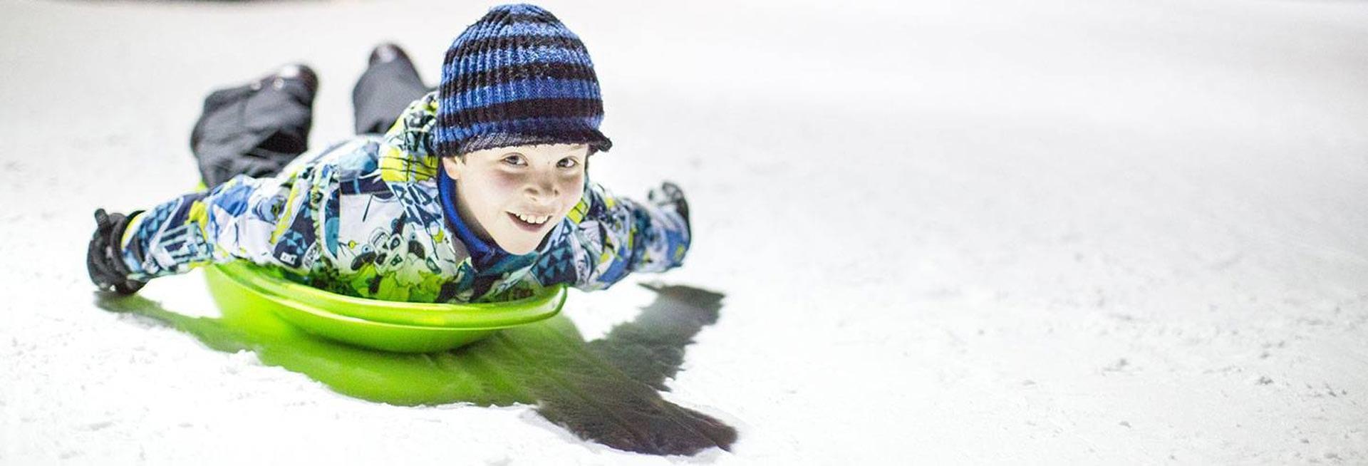 Boy sledding face first.